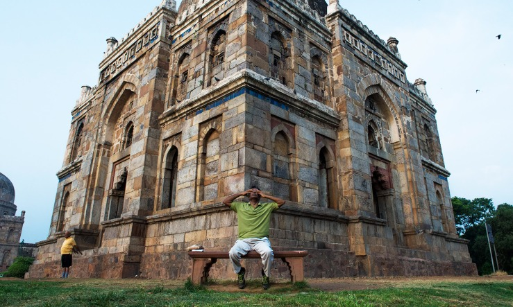 Indian Yoga practitioner Goverdhan, sits in front of a monument as he practices yoga in Lodhi Gardens in New Delhi on June 21, 2016, on International Yoga Day. A large group of yoga practicioners gathered at the park to mark International Yoga Day but Goverdhan sat away from the group and completed the same morning ritual he has done for the past 14 years since moving to a colony near the park.  / AFP PHOTO / ROBERTO SCHMIDT