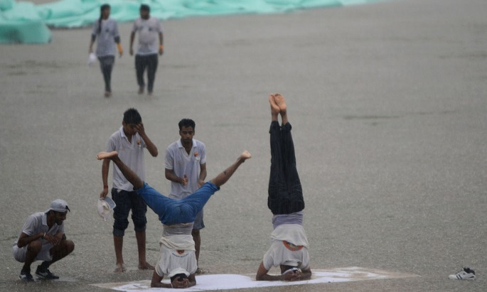 Indian yoga practitioneers take part in a session during heavy rains on International Yoga Day in Jammu on June 21, 2016. / AFP PHOTO / -