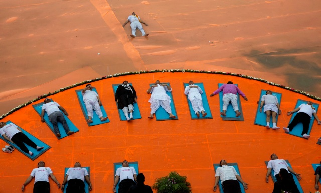 Indian Home Minister Rajnath Singh, center in middle row, performs yoga with others at an event to celebrate International Yoga Day in Lucknow, India, Tuesday, June 21, 2016. Millions of yoga enthusiasts are bending their bodies in complex postures across India as they take part in a mass yoga program to mark the second International Yoga Day. (AP Photo/Rajesh Kumar Singh)