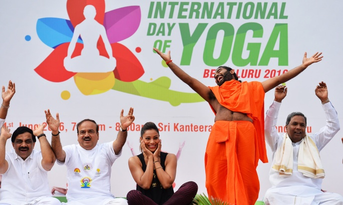 Yoga guru Vachanaananda (2R) conducts a laughter session with Chief Minister of Karnataka Siddaramaiah (R), Union Minister for Fertilizer Ananth Kumar (2L), and Bollywood actress Bipasha Basu (C) at a yoga session to mark International Yoga Day in Bangalore on June 21, 2016. / AFP PHOTO / Manjunath Kiran
