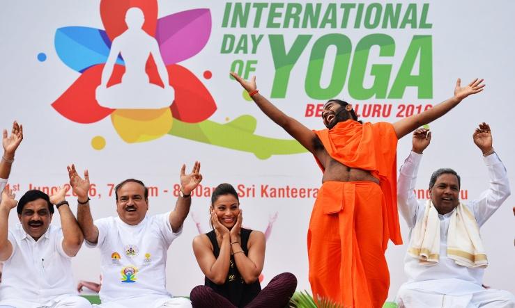 Yoga guru Vachanaananda (2R) conducts a laughter session with Chief Minister of Karnataka Siddaramaiah (R), Union Minister for Fertilizer Ananth Kumar (2L), and Bollywood actress Bipasha Basu (C) at a yoga session to mark International Yoga Day in Bangalore on June 21, 2016. / AFP PHOTO / Manjunath Kiran