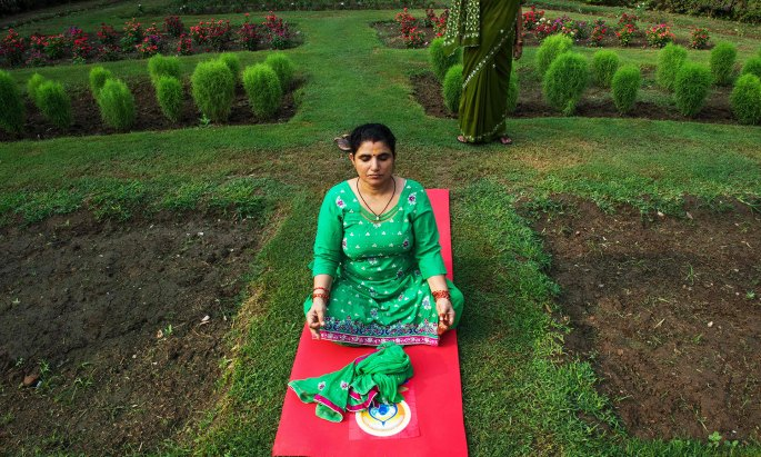 An Indian Yoga practitioner sits away from others as she participates in a morning yoga session to mark International Yoga Day in Lodhi Gardens in New Delhi on June 21, 2016 / AFP PHOTO / ROBERTO SCHMIDT