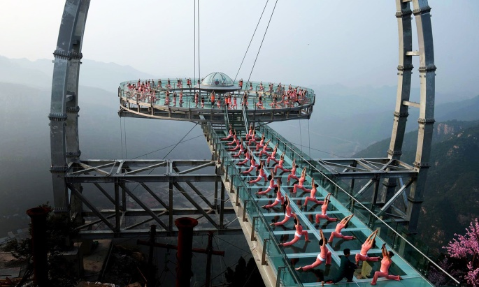 This photo taken on June 20, 2016 shows Chinese enthusiasts practicing yoga at a glass sightseeing platform in Shilinxia scenic area in Beijing. June 21 marks the International Yoga Day. / AFP PHOTO / STR / China OUT