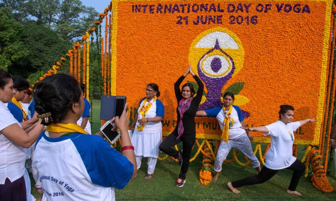 Indian Yoga practicioners pose in front of a floral arrangement after taking part in a morning yoga session to mark International Yoga Day in Lodhi Gardens in New Delhi on June 21, 2016. / AFP PHOTO / ROBERTO SCHMIDT