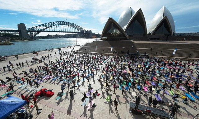 Sydneysiders enagage in a yoga event in front of the Australia's iconic landmark Opera House in Sydney on June 21, 2016.  Hundreds of Yoga lovers gathered at Opera House to mark the International  Yoga Day. / AFP PHOTO / Wendell Teodoro