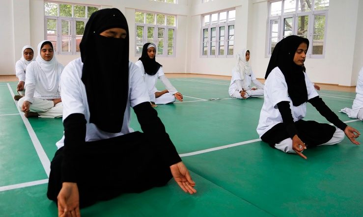 Kashmiri students perform yoga at an event to celebrate International Yoga Day in Srinagar, India, Tuesday, June 21, 2016. Millions of yoga enthusiasts are bending their bodies in complex postures across India as they take part in a mass yoga program to mark the second International Yoga Day. (AP Photo/Mukhtar Khan)