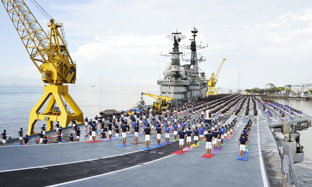 In this photograph released by the Indian Press Information Bureau (PIB) on June 21, 2016, Indian Armed Forces personnel take part in a yoga sesssion to mark International Yoga Day on the Indian Navy aircraft carrier INS Viraat in Mumbai.
